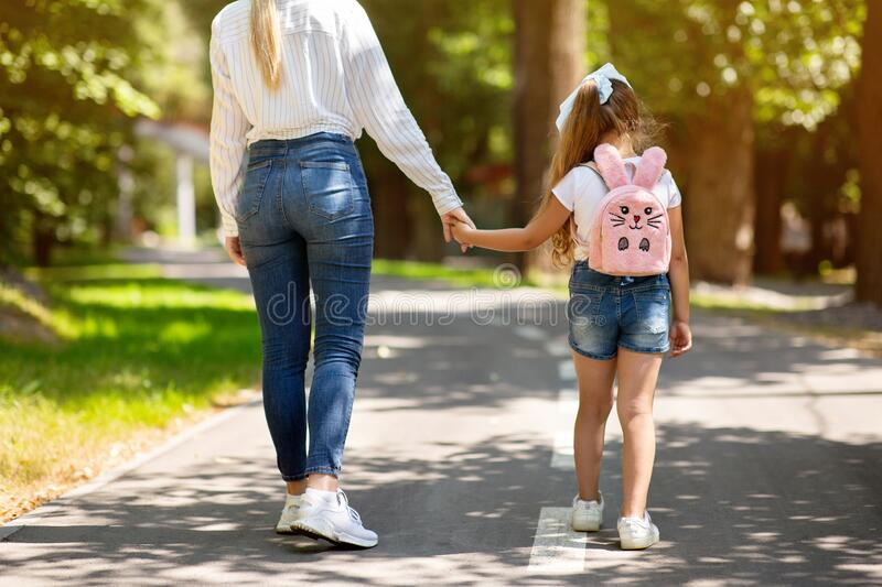 Mother And Daughter Walking Holding Hands In Park, Cropped