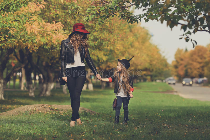 Mother and daughter walking holding hands at park. royalty free stock image