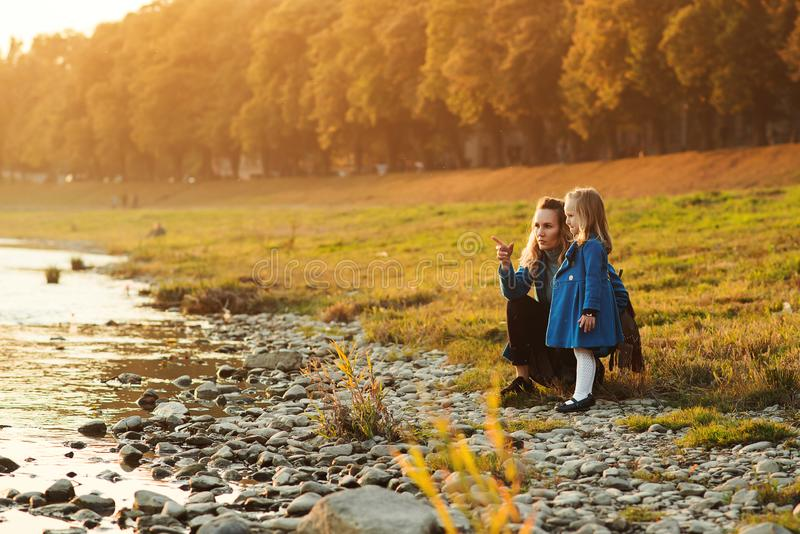 Mother and daughter walking near river in autumn time. Happy family. Fall weekend in the open air. Family enjoying beautiful autum stock photo