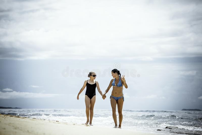Mother and daughter walking on the pristine tropical beach royalty free stock photo