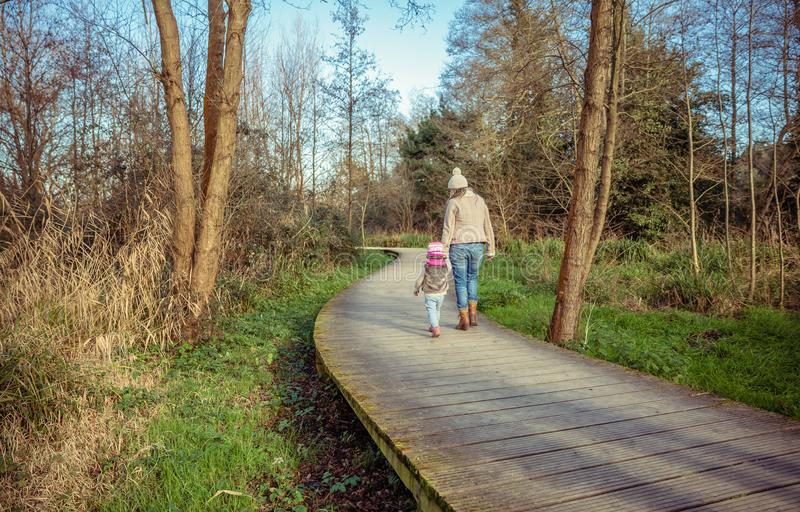 Mother and daughter walking together holding hands stock images