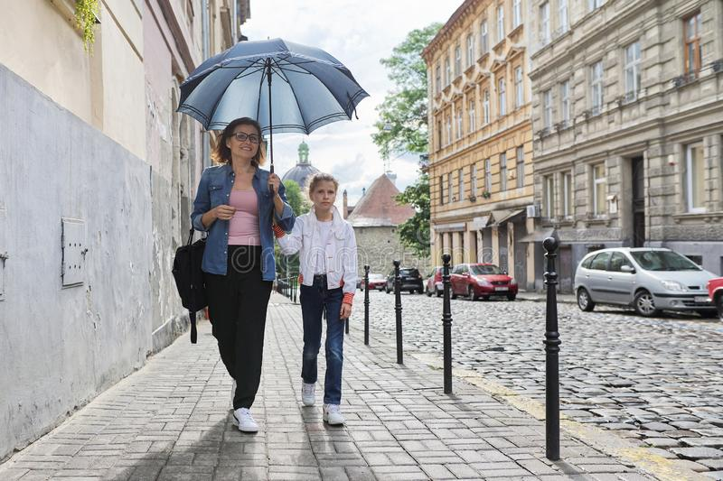 Mother and daughter walking under an umbrella along street. Rainy autumn weather in city, mother and daughter walking under an umbrella along street stock image
