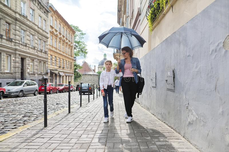 Mother and daughter walking under an umbrella along street. Rainy autumn weather in city, mother and daughter walking under an umbrella along street stock photography