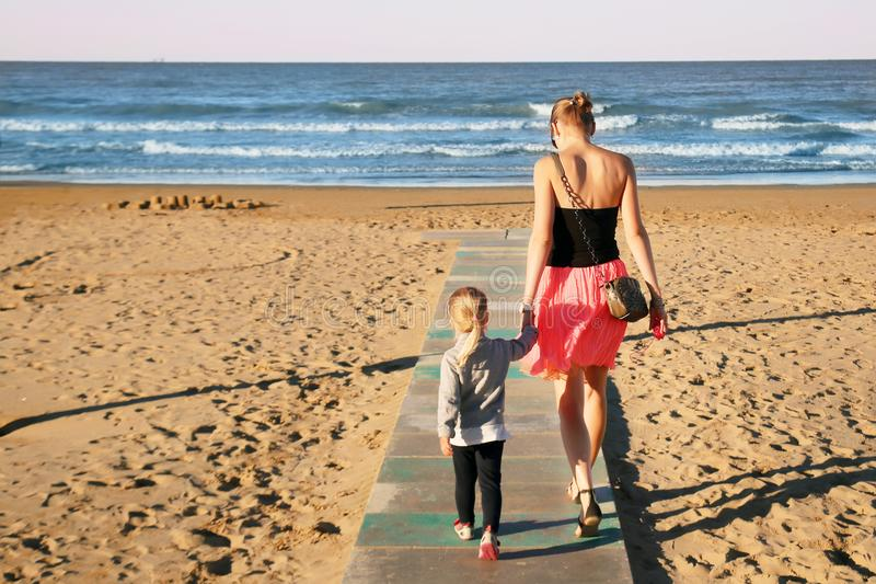 Mother and daughter walking by wooden flooring on sand beach at seaside. Summer family vacation. Children care and support by pare royalty free stock photography