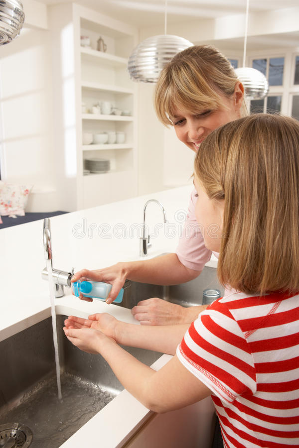 Download Mother And Daughter Washing Hands At Kitchen Sink Stock Photo - Image: 18745928