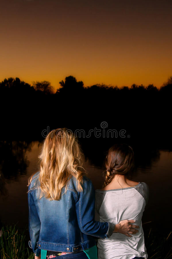 Mother and Daughter Watching the Sunset. A women and her teenage daughter watch the sunset with backs to the camera. The mom's hand is on her daughter's back in stock photo