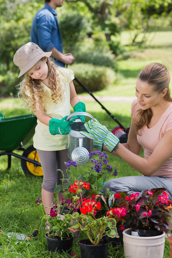 Mother with daughter watering plants. At the garden royalty free stock images