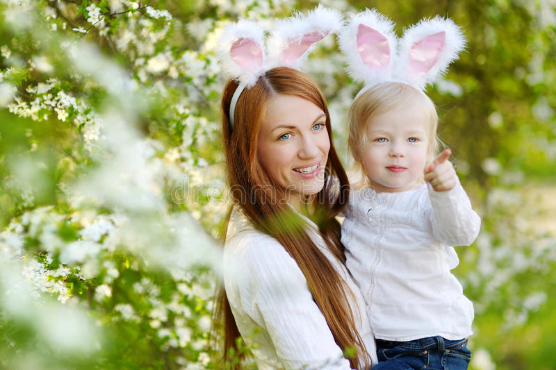 Mother and daughter wearing bunny ears on Easter. Young mother and her daughter wearing bunny ears in a spring garden on Easter day stock images