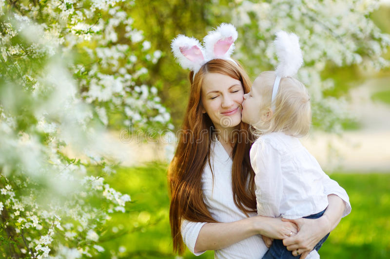 Mother and daughter wearing bunny ears on Easter. Young mother and her daughter wearing bunny ears in a spring garden on Easter day royalty free stock photography