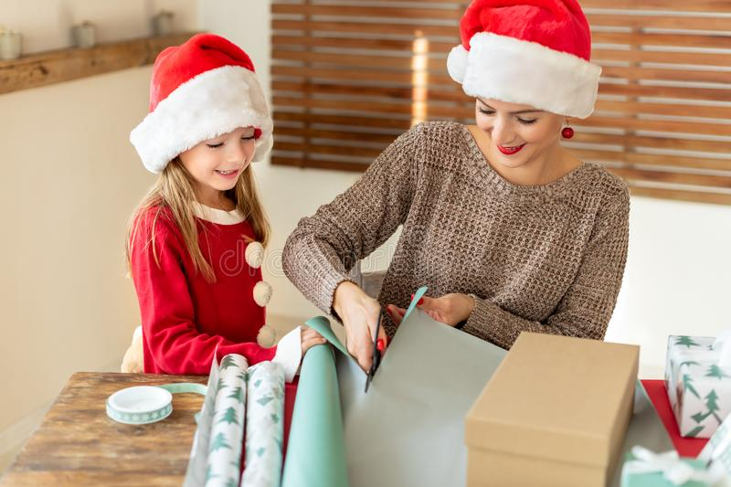Mother and daughter wearing santa hats having fun wrapping christmas gifts together in living room. Candid family christmas time. Mother and daughter wearing royalty free stock image
