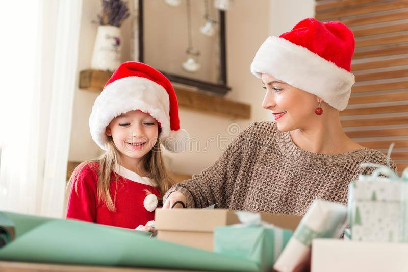 Mother and daughter wearing santa hats having fun wrapping christmas gifts together in living room. Candid family christmas time. Mother and daughter wearing royalty free stock photo