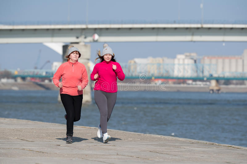 Mother and daughter wearing sportswear and running on windy day. At quay stock images