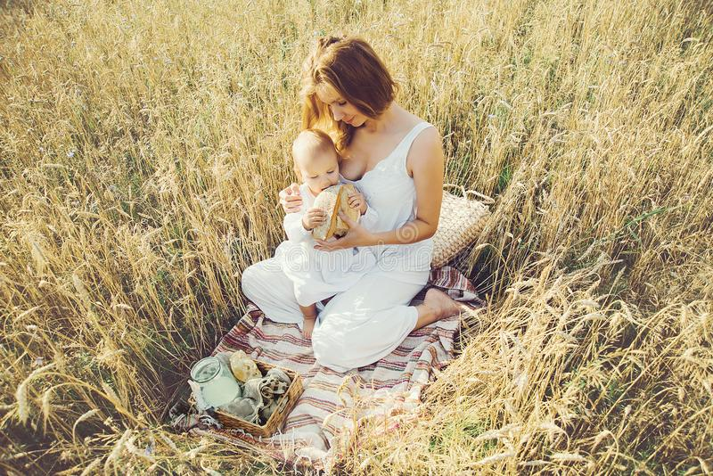 Mother and daughter in wheat field. Happy Family outdoors. healthy child with mother on picnic with bread and milk in golden cerea royalty free stock photo