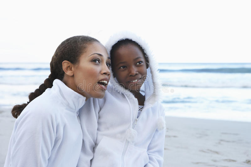 Mother and daughter (8-10) in white clothing on beach, woman crouching beside girl stock photography