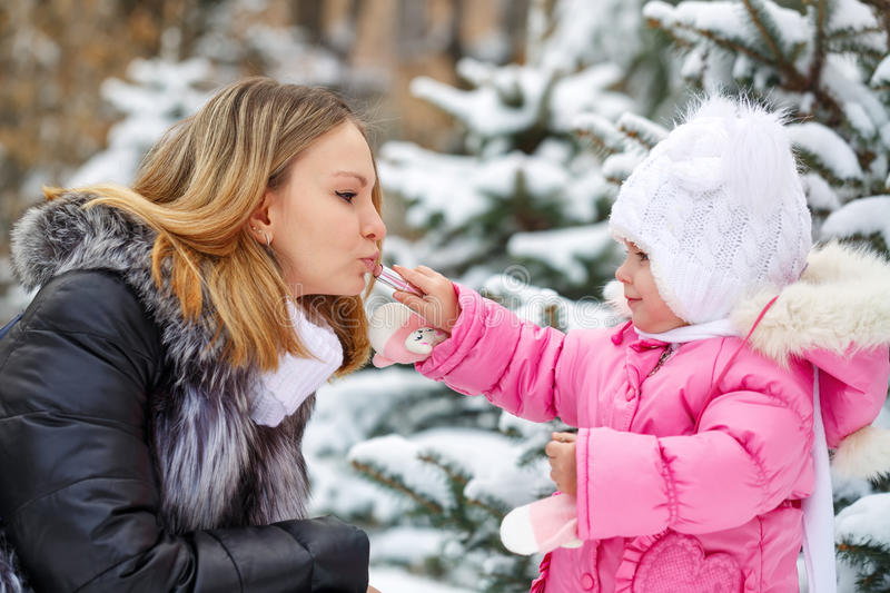Mother and daughter. Winter lipstick. Daughter gets hygienic lipstick on lips mother. Facial Skin Care. Family walk in a winter park royalty free stock photos