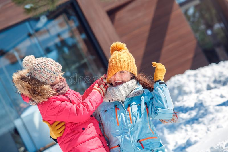 Winter vacation. Family time together outdoors daughter playing with mother taking off her hat laughing cheerful close stock photos