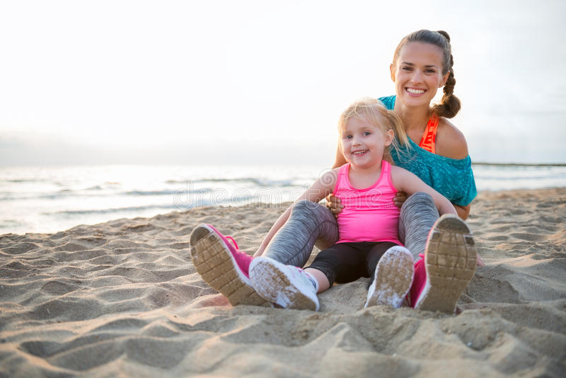 Mother and daughter in workout gear sitting together on beach royalty free stock image