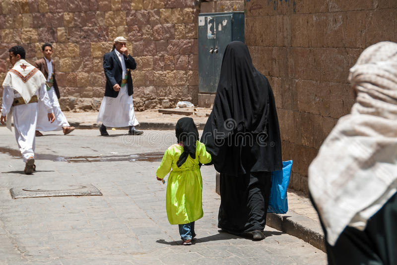 Mother and daughter in Yemen. An unidentified woman and her daughter in traditional dresses walk hand in hand in the local market on May 4, 2007 in Sanaa, Yemen royalty free stock images