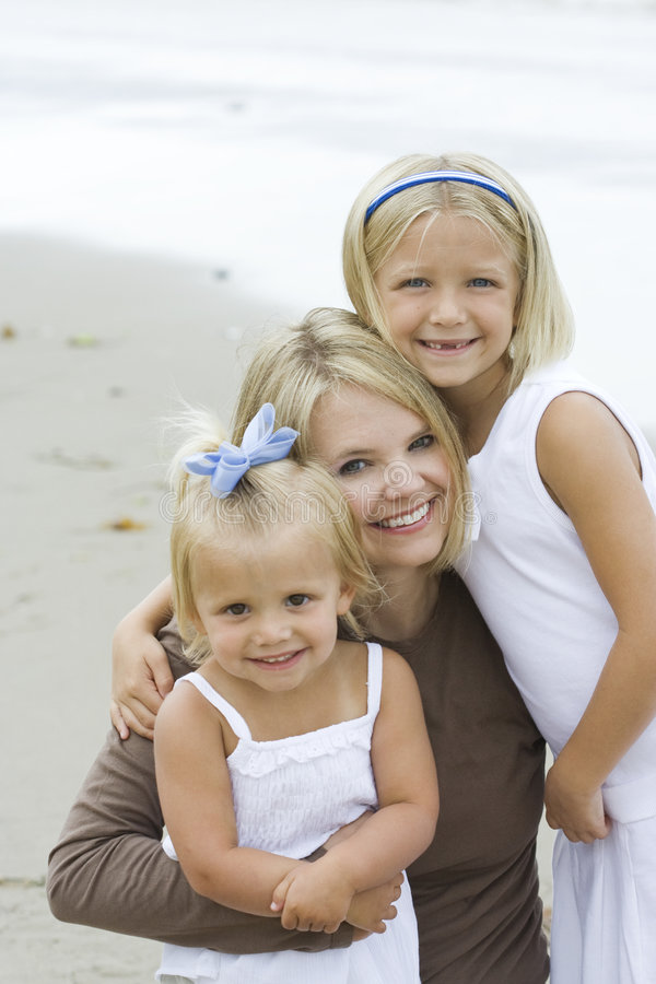 Mother and Daughters. A young mother and her blonde daughters huddle together in family unity with smiles on their faces