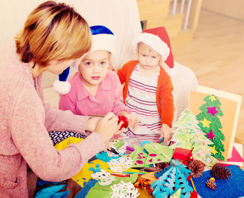 Mother with daughters doing applique work. Mother with two daughters doing applique work for Xmas stock images