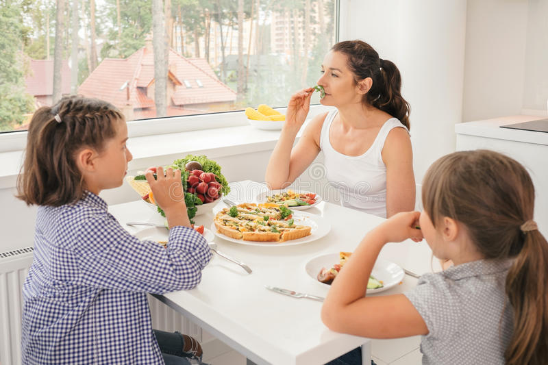 Mother and daughters eating healthy food in kitchen. Young mother and daughters eating healthy food in kitchen. Concept healthy lifestyle in modern family royalty free stock images