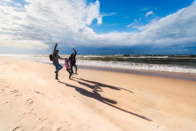 Mother with daughters jumping on the seaside beach on a sunny windy day - a family walk by the sea. Mother with two daughters jumping on the seaside beach on a stock photography