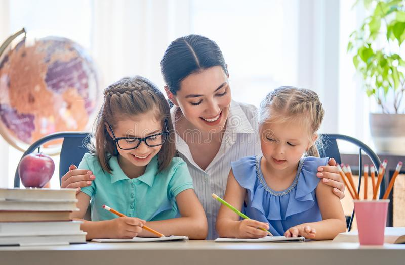 Mother and daughters are learning to write royalty free stock image