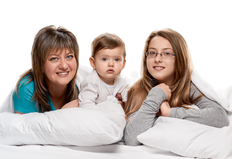 Mother and daughters on pillows. Portrait of a mother with her teenager and little daughters in the bed on white background royalty free stock photo