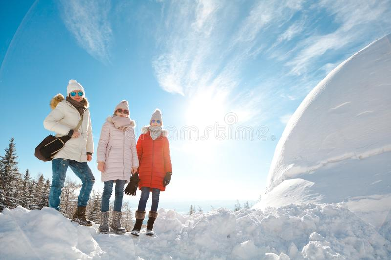 Mother with daughters posing on a snow stock images