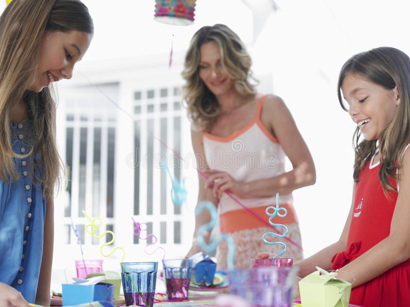 Mother With Daughters Preparing Birthday Party stock images