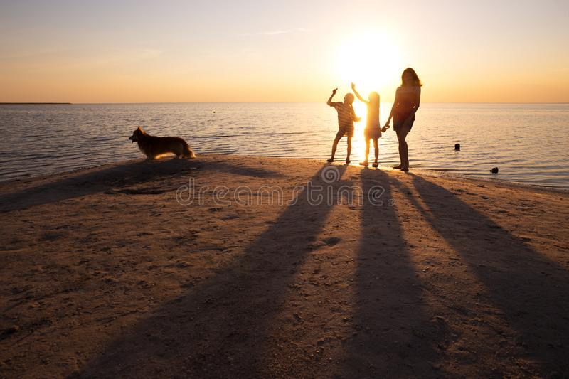 Mother and daughters  at the Sea of Azov. Mother, daughters and dog walking on the beach at sunset. Ukrainian landscape at the Sea of Azov, Ukraine royalty free stock photography