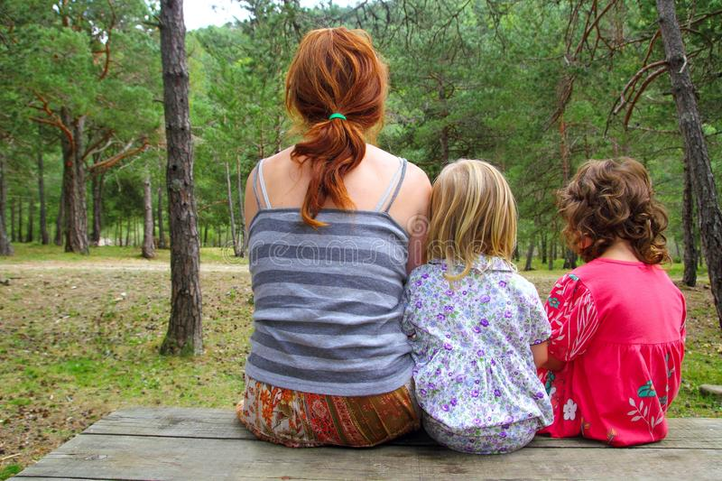 Mother and daughters sitting back park forest