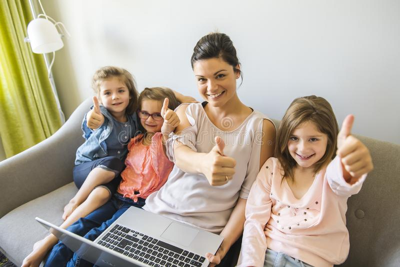 Mother and daughters on sofa at home using laptop stock images