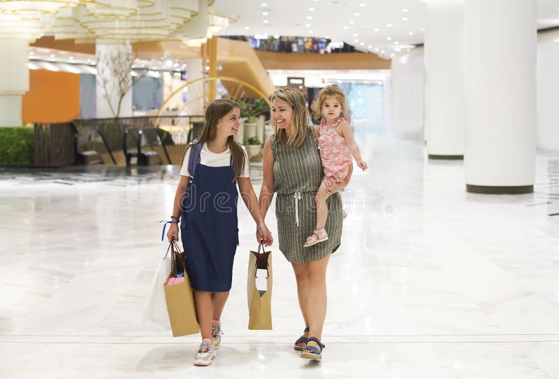 Mother and daughters walking with shopping bags royalty free stock image