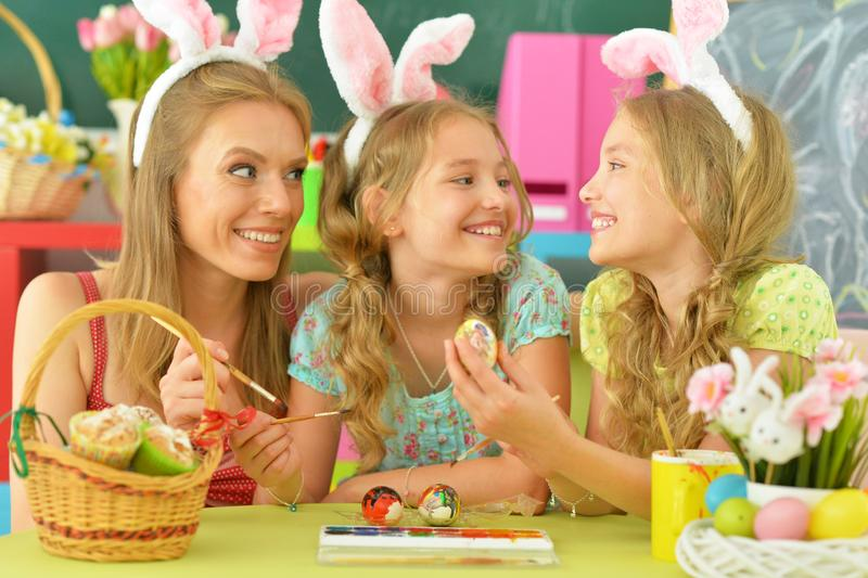 Mother with daughters wearing rabbit ears decorating Easter eggs stock photo