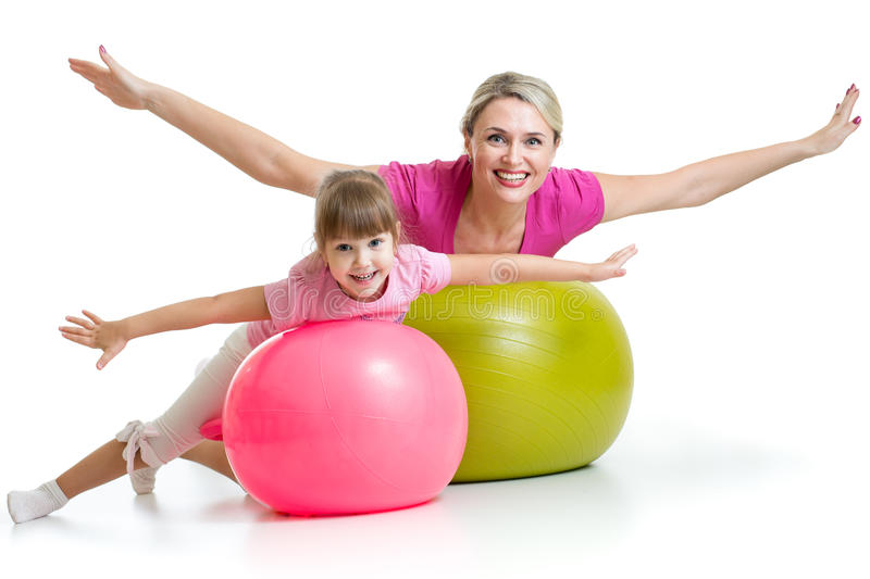 Mother doing gymnastics with daughter kid on fit ball. Mother doing gymnastics with daughter kid on fitness ball royalty free stock photography
