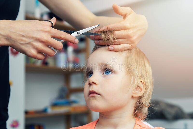 Mother doing haircut for her child at home stock images