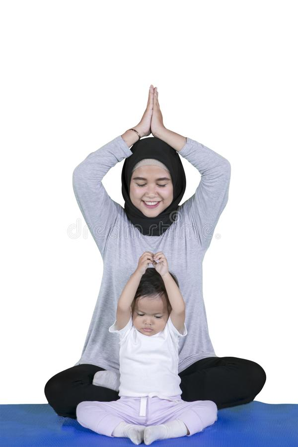 Mother doing yoga exercises with her daughter royalty free stock photo