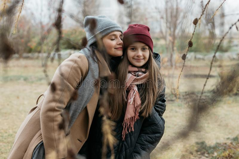 Mother and doughter teenager are walking on the street in warm autumn clothes stock photography