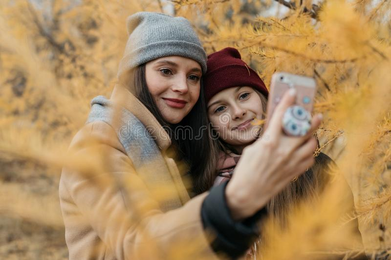 Mother and doughter teenager are walking on the street in warm autumn clothes royalty free stock image
