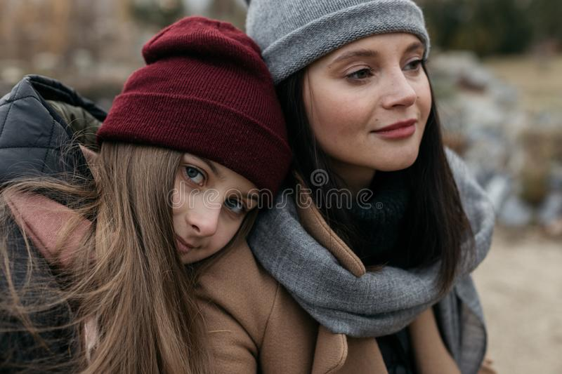 Mother and doughter teenager are walking on the street in warm autumn clothes royalty free stock photo