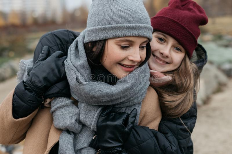Mother and doughter teenager are walking on the street in warm autumn clothes stock photo