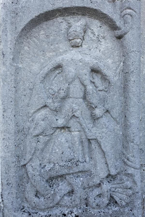 Mother of Dragons. Stone relief on a portal at Väte Church on Gotland which shows a woman who suckles two dragons royalty free stock images
