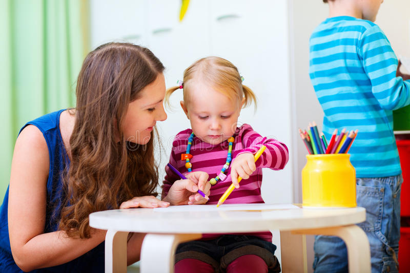 Mother drawing together with her daughter. Young mother and her daughter drawing together. Also perfect for kindergarten daycare context royalty free stock images