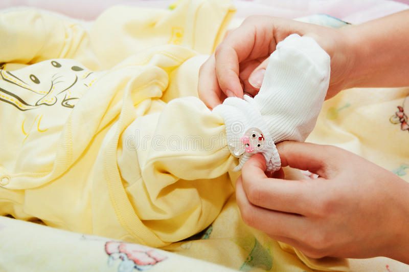 Mother dresses her baby royalty free stock photo