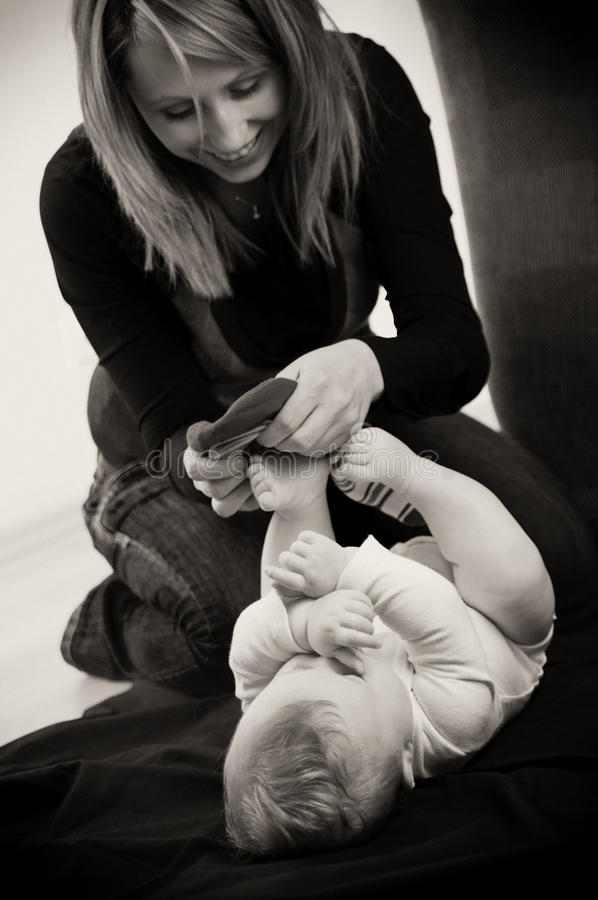 Mother Dressing Baby Boy Stock Images