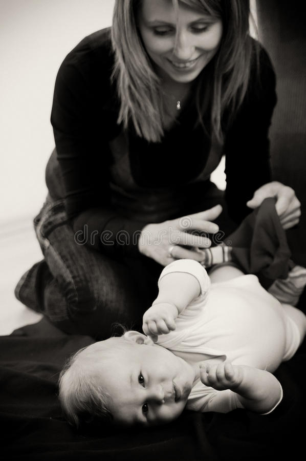 Mother dressing baby son. Monochromatic image of a mother dressing her baby son stock photos