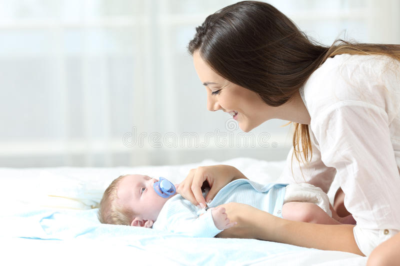 Mother dressing her baby son. Side view portrait of a happy mother dressing her baby son on a bed at home stock photography