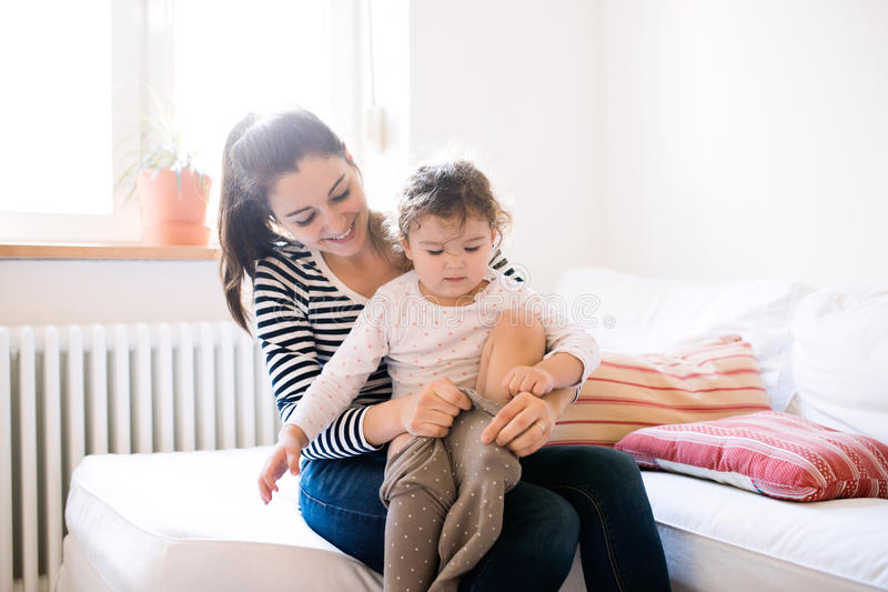 Mother dressing her daughter in the morning on a couch stock photography