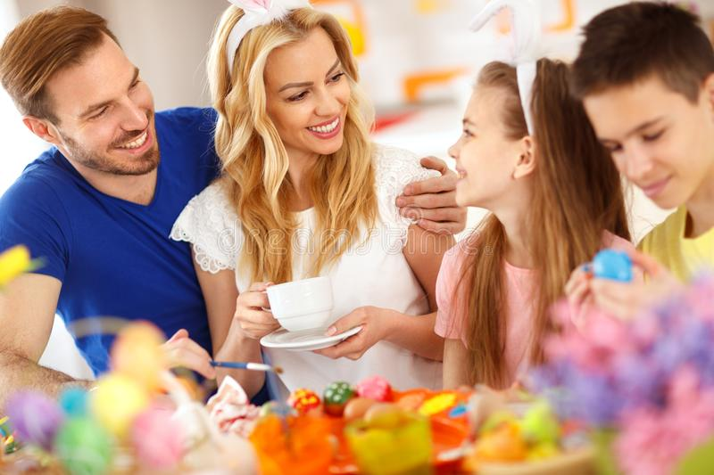 Mother drinks coffee while children coloring Easter eggs stock photos